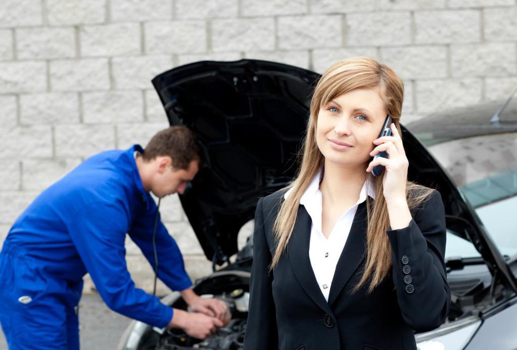 Девушка звонит по телефону, пока специалист чинит машину