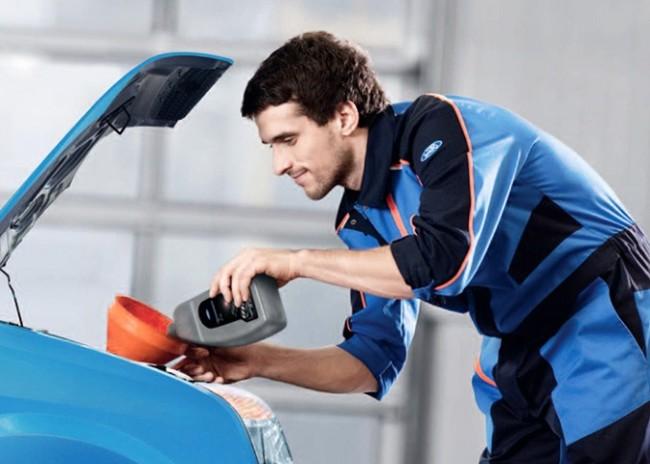 Автомеханик меняет масло в авто