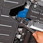 3. Теперь подставьте емкость под фильтр. Демонтируйте его при помощи специального ключа или руками. Если не получается, проткните его отверткой и используйте ее в качестве рычага.
