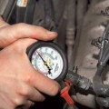 Проверка уровня компрессии при помощи компрессометра