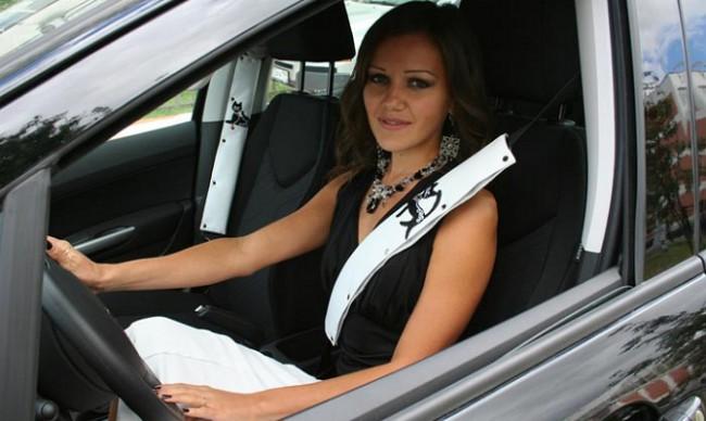 Девушка за рулем авто, пристегнутая ремнем безопасности с накладкой