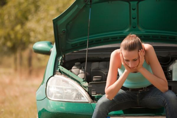 Отчаянная девушка рядом с поломанным авто
