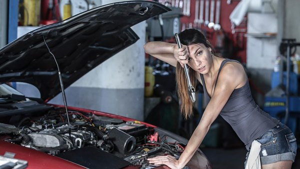 Девушка выполняет ремонт машины